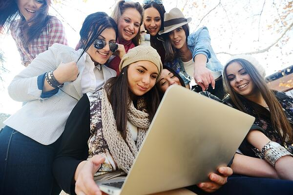 Happy teen girls having good fun time outdoors using laptop